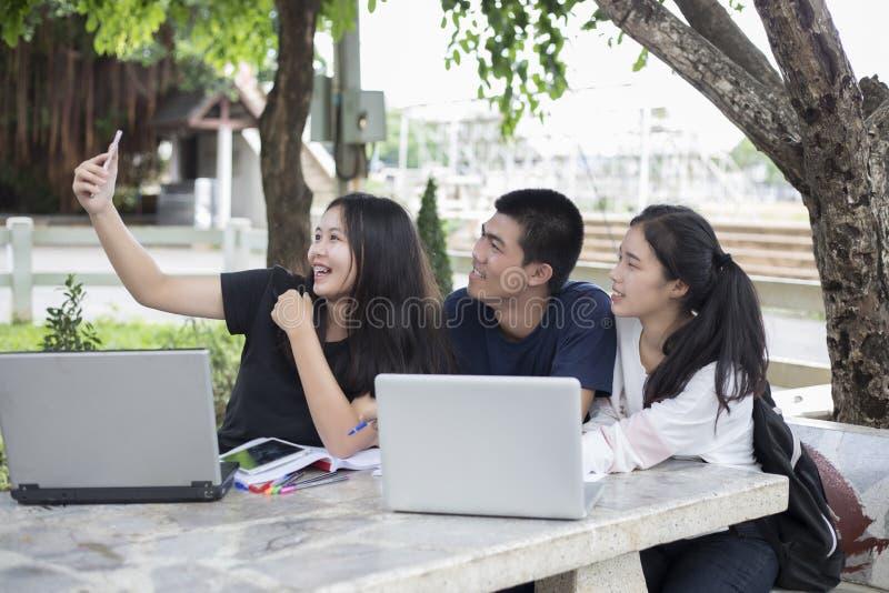 Asiatisk grupp av studenter som använder minnestavlan och anteckningsboken som delar med t royaltyfri bild