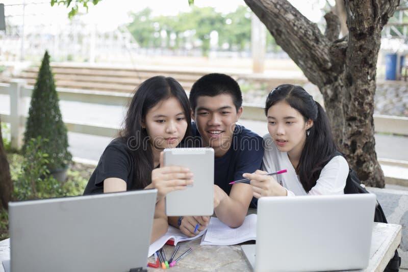 Asiatisk grupp av studenter som använder minnestavlan och anteckningsboken som delar med t royaltyfri fotografi