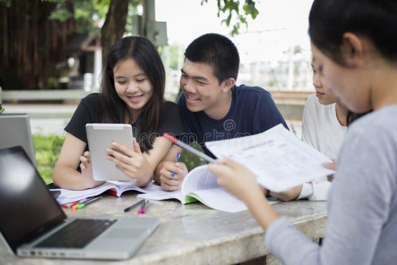 Asiatisk grupp av studenter som använder minnestavlan och anteckningsboken som delar med t royaltyfri foto