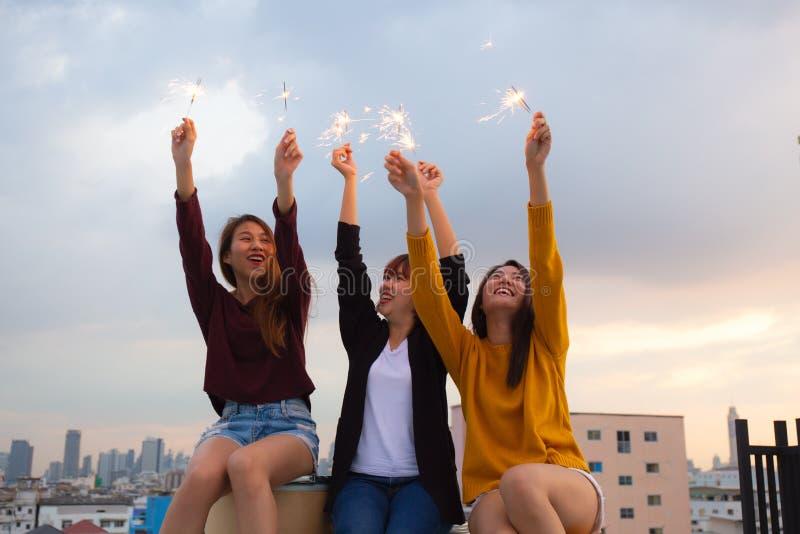 Asiatisk grupp av vänner som tänder tomtebloss och tycker om frihet på solnedgången, asiatisk kvinna som lyckligt rymmer tomteblo arkivbild
