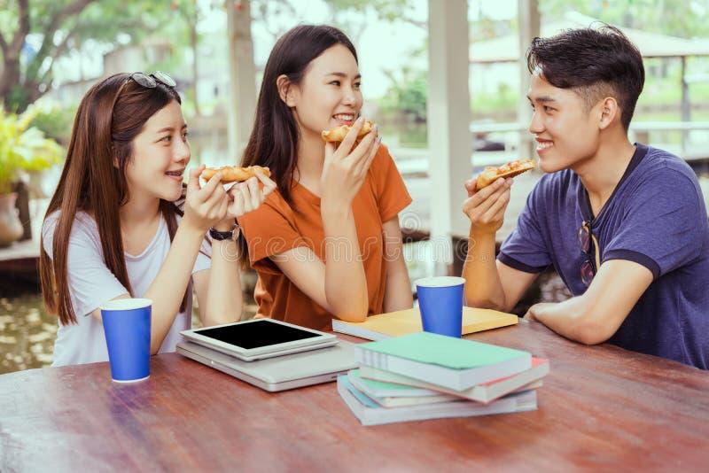 Asiatisk grupp för studenter som äter tillsammans pizza, i avbrott av tid royaltyfria bilder