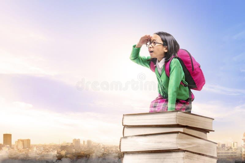 Asiatisk gullig flicka med exponeringsglas och ryggsäcken som sitter på högen av böcker med bakgrund för stad och för blå himmel royaltyfri foto