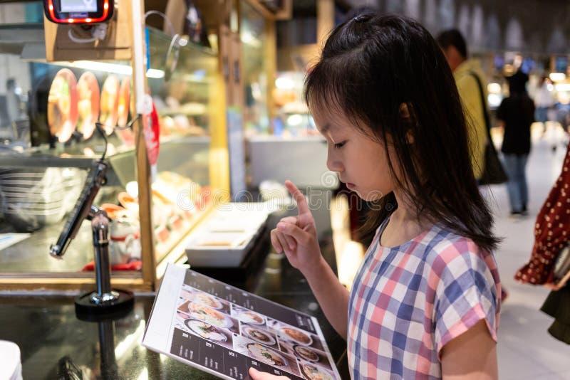 Asiatisk gullig flicka som beställer från meny royaltyfria foton