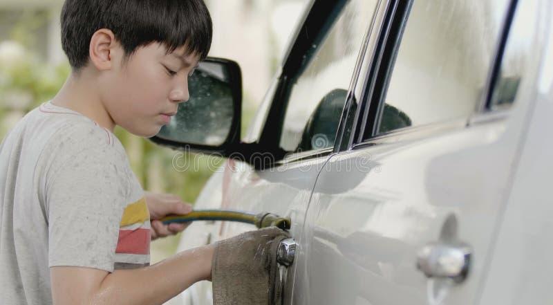 Asiatisk gullig pojkewash en bil med leendeframsidan royaltyfria foton