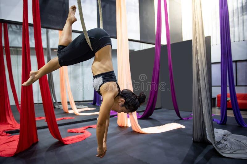 Asiatisk gymnastflicka som h?nger p? flyg- beslag arkivfoto