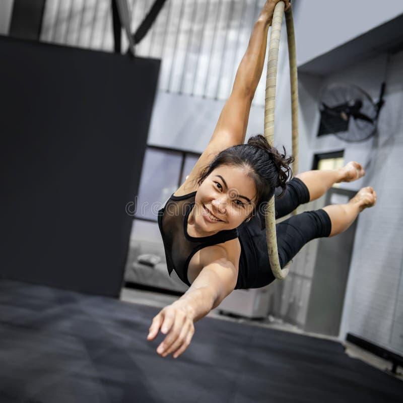 Asiatisk gymnastflicka som h?nger p? flyg- beslag arkivfoton