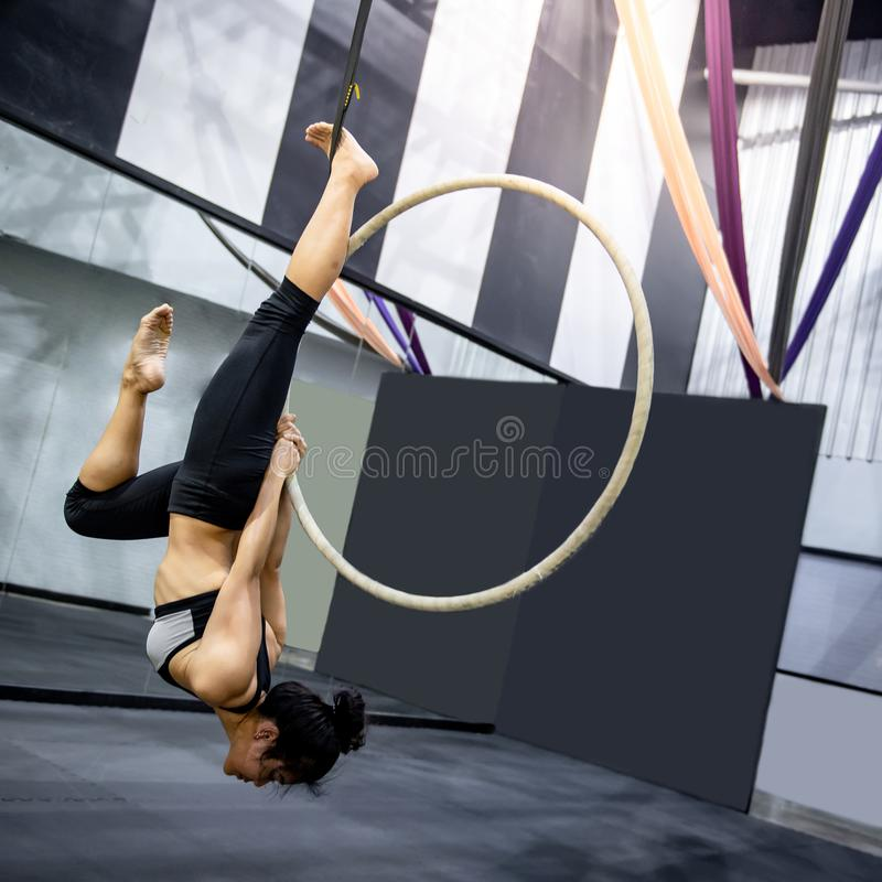 Asiatisk gymnastflicka som h?nger p? flyg- beslag royaltyfria foton