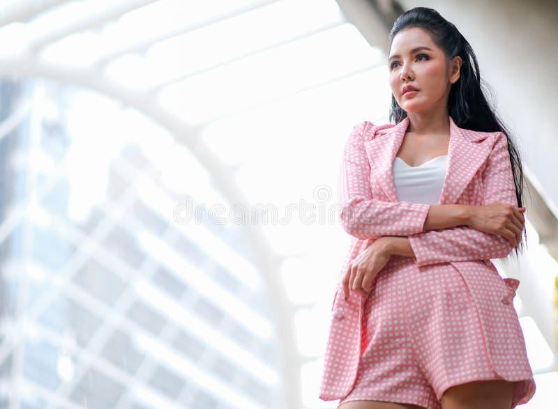 Asiatisk härlig affärsflicka med rosa klänninghandling som säker och ställning bland hög byggnad i storstaden i dagtid arkivfoto