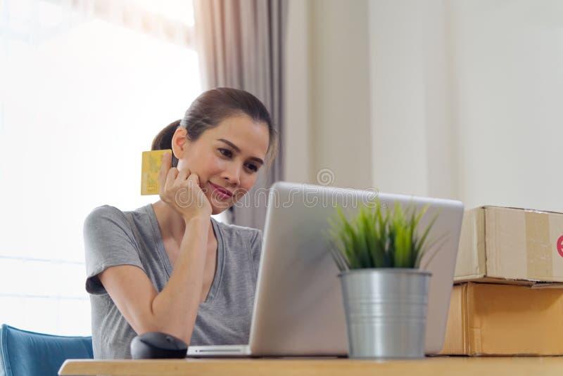 Asiatisk härlig flicka som direktanslutet köper från websiten genom att använda kreditkorten för betalning arkivbild