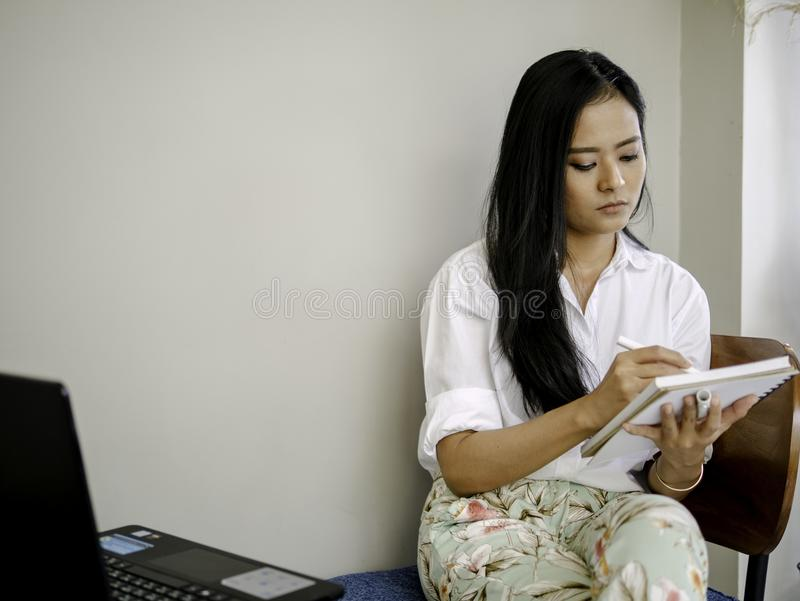 Asiatisk härlig freelancerlönuppmärksamhet som ner tar anmärkningar, handstil eller teckningskreativitetbegrepp arkivbilder
