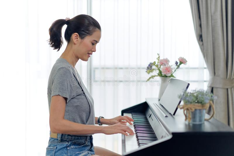 Asiatisk härlig kvinna som hemma spelar det elektroniska pianot Sett från sidosikt medan henne som trycker på pianotangenter vid  royaltyfria bilder