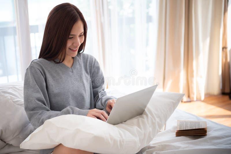 Asiatisk härlig kvinna som skriver på hennes bärbar dator fotografering för bildbyråer