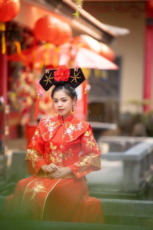 Asiatisk härlig ung kvinna som bär en traditionell kinesisk brudklänning arkivfoton