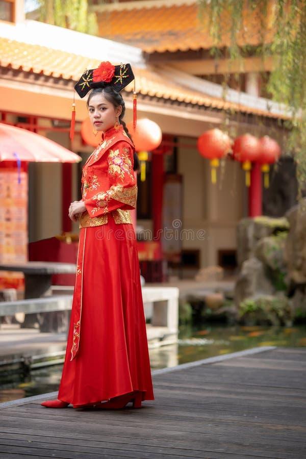 Asiatisk härlig ung kvinna som bär en traditionell kinesisk brudklänning, arkivbilder