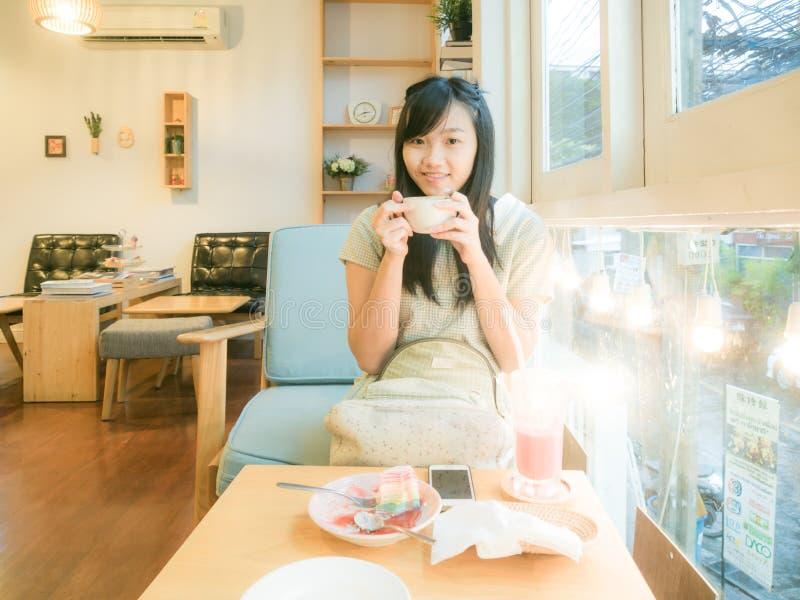 Asiatisk härlig ung kvinna som dricker kaffe nära fönster arkivfoton