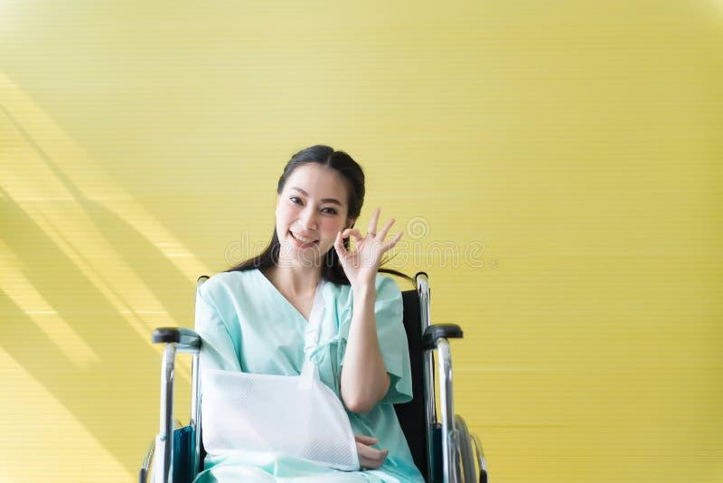 Asiatisk härliga kvinnapatienter att lyfta upp ditt reko teckensymbol för hand och att sitta på rullstolen på sjukhuset, lyckligt arkivfoto