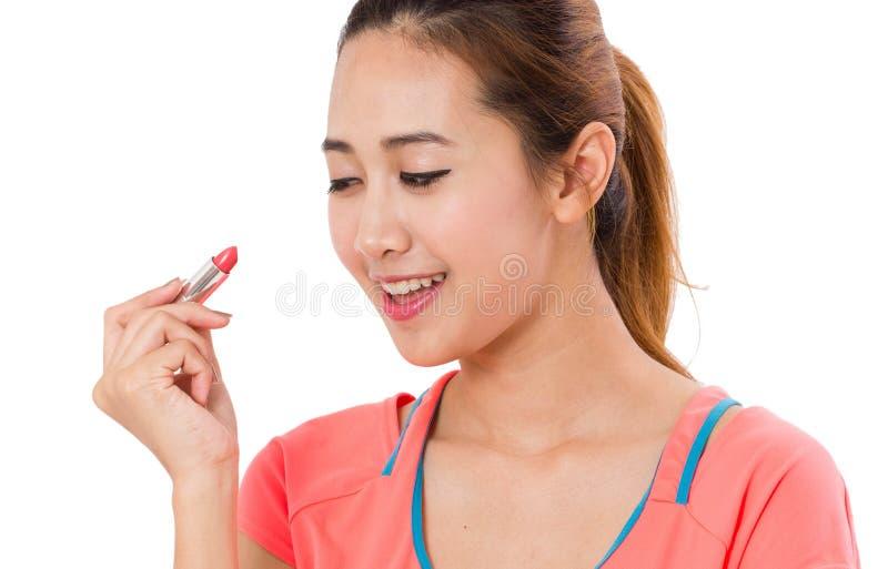 Asiatisk hållande läppstift för ung kvinna royaltyfria bilder