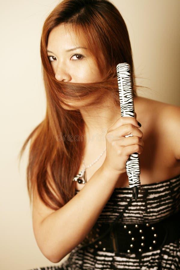 asiatisk hårstraightener som använder kvinnan arkivfoto