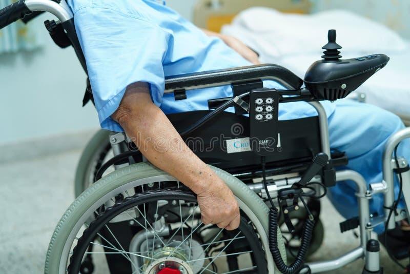 Asiatisk hög eller äldre kvinnapatient för gammal dam på den elektriska rullstolen med fjärrkontroll på att vårda sjukhussalen fotografering för bildbyråer