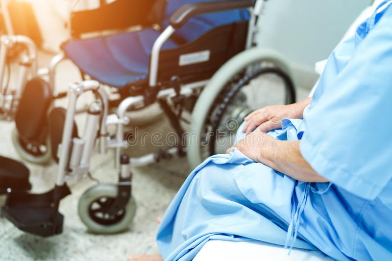 Asiatisk hög eller äldre kvinnapatient för gammal dam som sitter på säng med rullstolen, i att vårda sjukhussalen: sunt starkt me royaltyfri bild