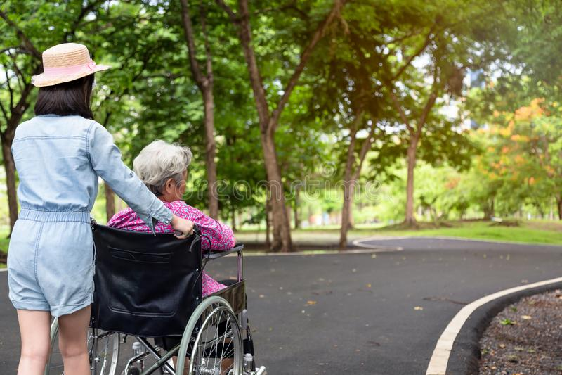 Asiatisk hög kvinna i rullstol med flickan för litet barn som stöttar den rörelsehindrade morföräldern på att gå den gröna nature royaltyfria foton