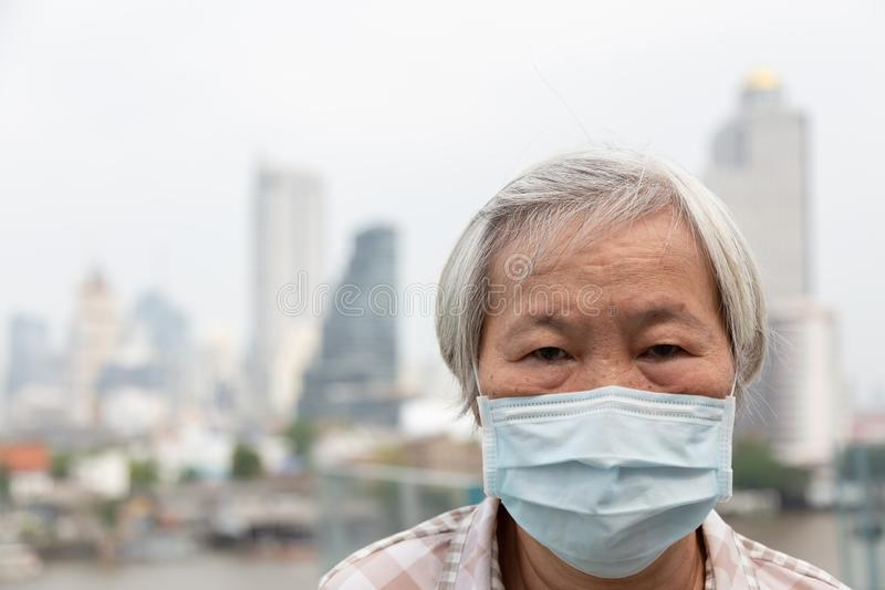 Asiatisk h?g kvinna med skydd f?r framsidamaskering, b?rande framsidamaskering f?r ?ldre kvinna p? grund av luftf?rorening i stad royaltyfri bild