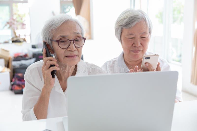 Asiatisk hög kvinna och vän med bärbar datordatoren, lyckligt le äldre folk som håller ögonen på något intressera, medan rymma royaltyfri bild