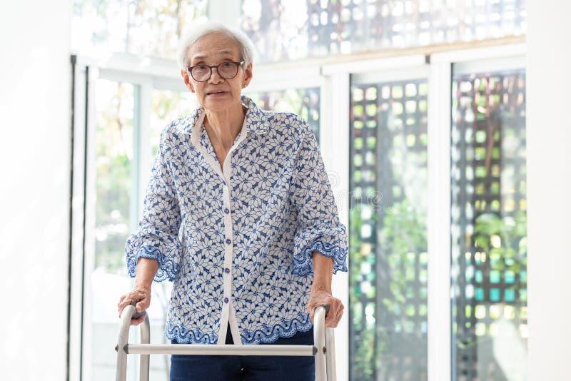 Asiatisk hög kvinna som använder fotgängaren under rehabilitering, äldre kvinna med att gå och att öva hemma royaltyfria foton