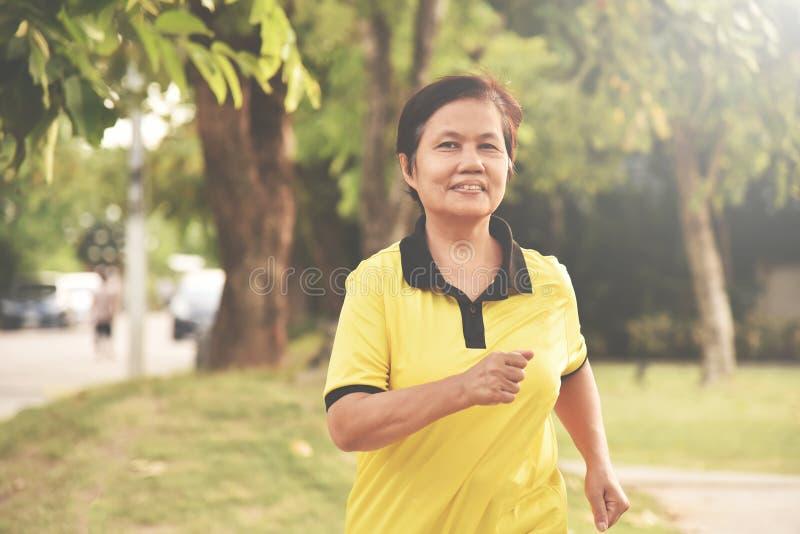 Asiatisk hög kvinna som kopplar av med att jogga fotografering för bildbyråer