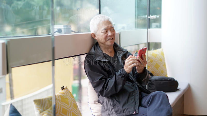 Asiatisk hög man som använder den smarta telefonen Meddela till och med technolo arkivbilder