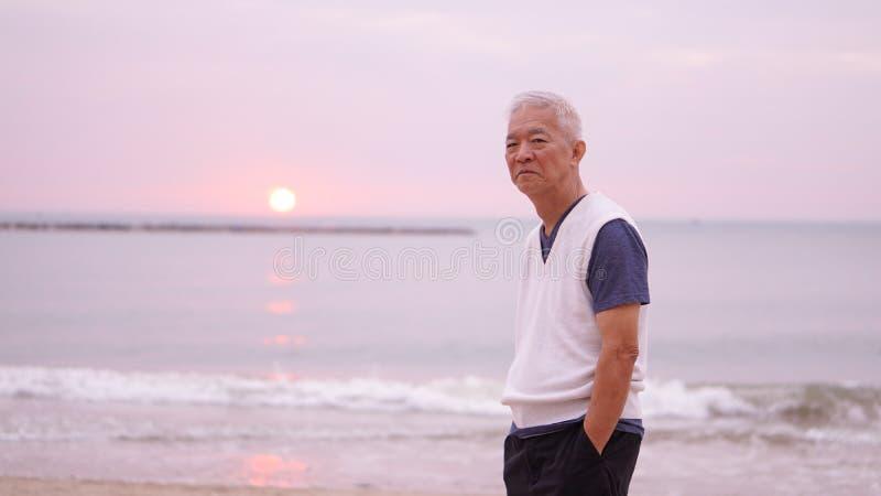 Asiatisk hög man som bara står på utrymme för soluppgångmorgonkopia arkivbild