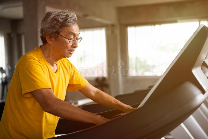 asiatisk hög man som går övning på trampkvarngenomkörare i konditionidrottshall sport trainnig, pensionerat, äldre, moget som är  royaltyfri fotografi