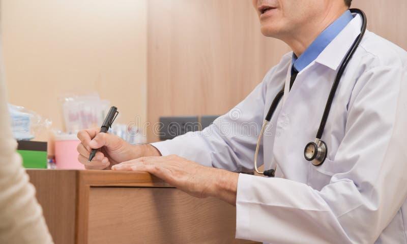 Asiatisk hög manlig doktor som talar med den kvinnliga patienten arkivbilder