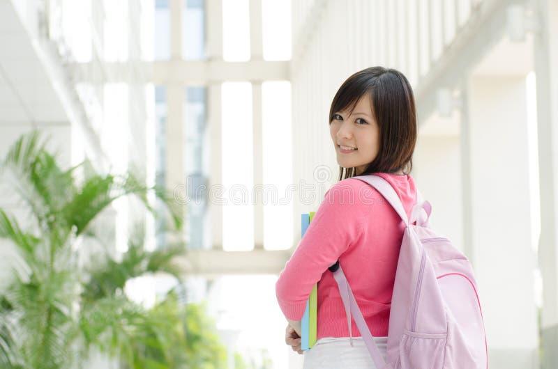 Asiatisk högskolaflickastudent på skolauniversitetsområdet fotografering för bildbyråer