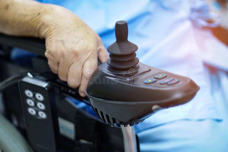 Asiatisk h?g eller ?ldre kvinnapatient f?r gammal dam p? den elektriska rullstolen med fj?rrkontroll p? att v?rda sjukhussalen royaltyfria bilder