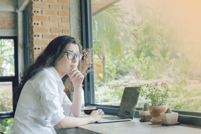 asiatisk h?rlig kvinna sitt i kafé för att shoppa för att se ut sidofönstret med den allvarliga framsidan E-kommers universitetut arkivfoton