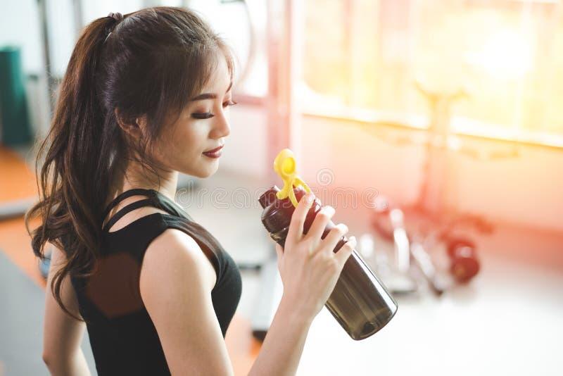Asiatisk h?rlig kvinna som dricker proteinskakan eller dricksvatten i idrottshall f?r sportkonditionutbildning Sportar och folkbe arkivbild