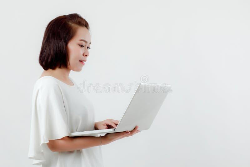 Asiatisk h?rlig kvinna som st?r i en vit skjorta i hennes hand som rymmer en st?llning f?r b?rbar datordator som lyckligt ler med fotografering för bildbyråer