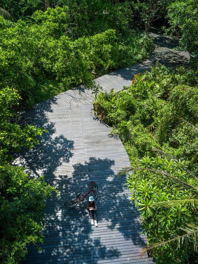 Asiatisk handelsresandeferie kopplar av med cykeln i natur parkerar royaltyfri foto
