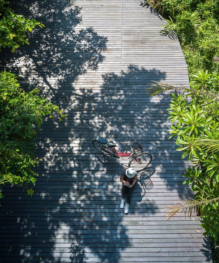 Asiatisk handelsresandeferie kopplar av med cykeln i natur parkerar royaltyfria bilder