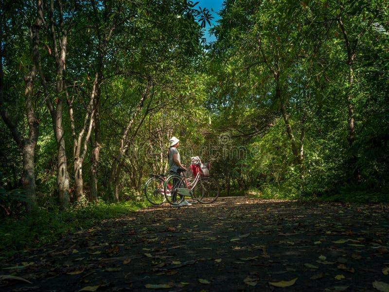 Asiatisk handelsresandeferie kopplar av med cykeln i natur parkerar royaltyfri fotografi