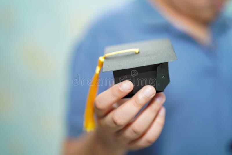 Asiatisk hatt för mellanrum för avläggande av examen för håll för ung unge för barn på trätabellen i skola royaltyfri foto