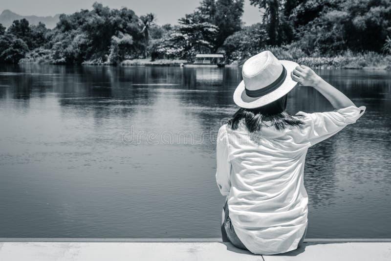 Asiatisk hatt för väv för kvinnakläder och vit skjorta som sitter på träterrass och framåtriktat ser till floden royaltyfria foton