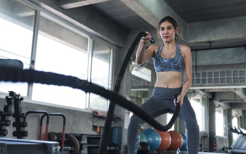 Asiatisk idrottskvinnapassformutbildning med stridrepet i konditionidrottshall Sport- och genomk?raremotivationbegrepp arkivbilder