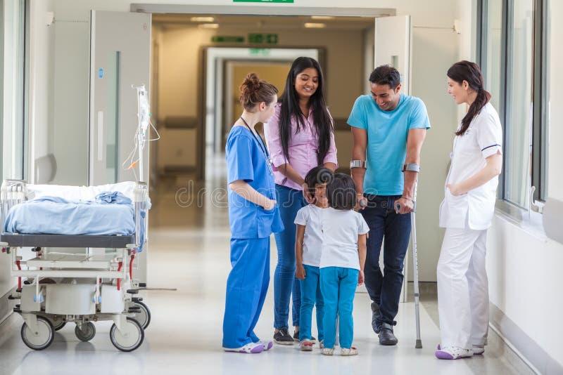 Asiatisk indisk familj, doktor och sjuksköterska i sjukhuskorridor arkivfoton