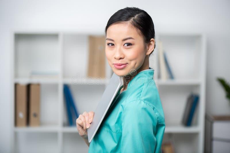 Asiatisk internist som använder den digitala minnestavlan i yrkesmässig klinik arkivfoto