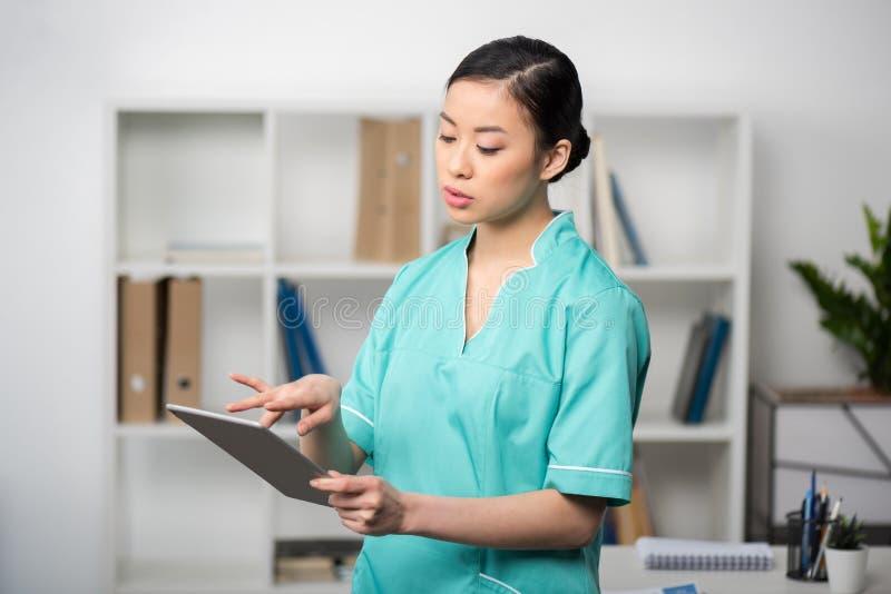 Asiatisk internist som använder den digitala minnestavlan i yrkesmässig klinik royaltyfri fotografi