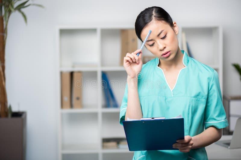 Asiatisk internist som ser skrivplattan med diagnos i yrkesmässig klinik royaltyfri bild