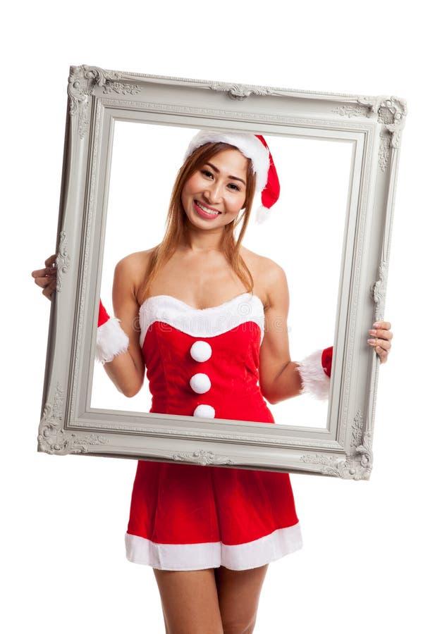 Asiatisk julflicka med den Santa Claus kläder och ramen royaltyfri fotografi