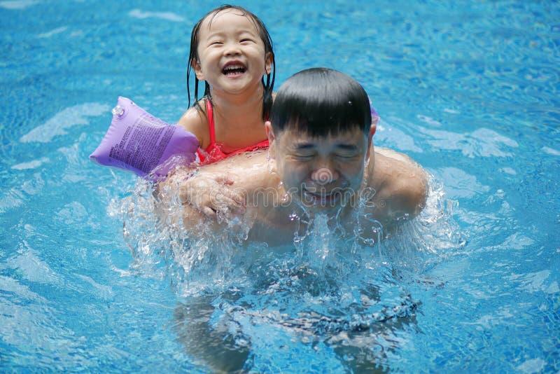 Asiatisk kinesisk fader och dotter som har gyckel i simbass royaltyfri foto